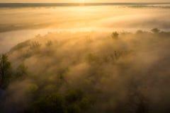 Nascer do sol sobre o riverbank nevoento Névoa na opinião aérea do rio Rio enevoado na luz solar de cima de imagens de stock