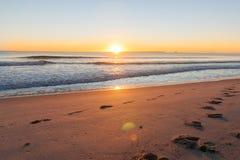 Nascer do sol sobre pegadas na praia foto de stock royalty free