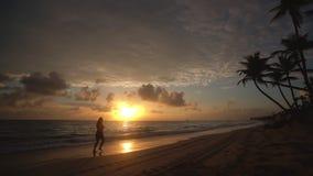 Nascer do sol sobre a praia tropical em Punta Cana, República Dominicana Mulher Running vídeos de arquivo