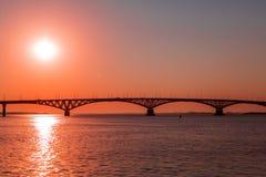 Nascer do sol sobre uma ponte da estrada através do Rio Volga entre as cidades de Saratov e Engels, Rússia Imagem de Stock