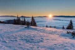 Nascer do sol surpreendente da montanha acima das baixas nuvens da inversão Foto de Stock