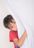 Nascondendosi dietro la tenda fotografia stock libera da diritti