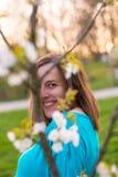 Nascondersi castana splendido sorridente dietro i fiori di ciliegia Immagine Stock
