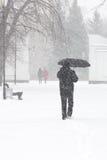 Nascondersi pedonale maschio dalla neve sotto l'ombrello, verticale Fotografia Stock