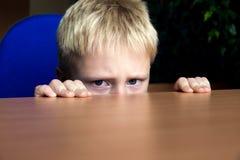 Nascondersi triste del bambino Immagini Stock