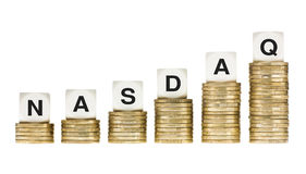 NASDAQ Stock Exchange Letters on Stacks of Gold Coins Royalty Free Stock Photography