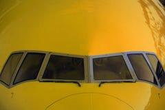 Nase eines gelben Flugzeuges mit Fenstern des Cockpits Lizenzfreie Stockfotografie