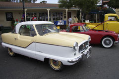 Nash Metropolitan 1961 at Car Show. American subcompact vintage car (Nash Metropolitan 1961) in the foreground and visitors Car Show in the background Stock Image