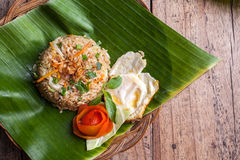 Nasi Goreng with fried egg. Decorated with tomato on palm leave from above Stock Photography