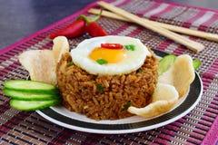 Nasi goreng stekte ris med räkor och ägget som garnerades med nya gurkaskivor och räkasmällare på en platta på a arkivbilder