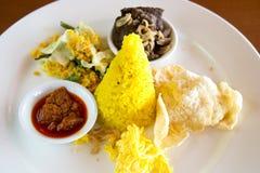 Nasi Kuning Indonesian amarela o arroz servido com carne assada, o ovo shredded, os vegetais, a salada do coco, o sambal caseiro  imagem de stock