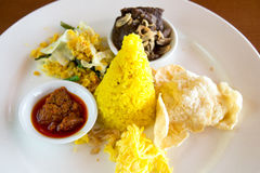 Free Nasi Kuning Indonesian Yellow Rice Served With Braised Beef, Shredded Egg, Vegetables, Coconut Salad, Homemade Sambal And Crackers Stock Image - 73485081