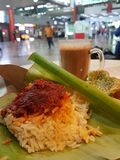 Nasi Lemak in Banana Leaf with Hot Drinks on Blur Background Stock Photos