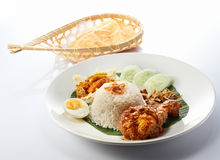 Nasi Lemak Chicken Drumstick Rendang. Isolated Nasi Lemak Chicken Drumstick Rendang with Crackers in White Background Stock Photo