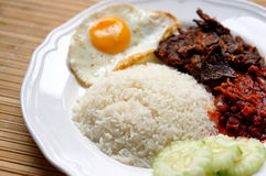 Nasi lemak (coconut rice). Served with sunny side up egg, hot spicy fried beef lungs and hot spicy sauce. Nasi lemak is a fragrant rice dish cooked in coconut Royalty Free Stock Photography