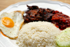 Nasi lemak (coconut rice). Served with sunny side up egg, hot spicy fried beef lungs and hot spicy sauce. Nasi lemak is a fragrant rice dish cooked in coconut Royalty Free Stock Image