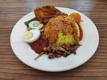Nasi Lemak dient met gesneden kippenkerrie, ei, komkommer, ansjovissen, aardnoot en sambal stock fotografie