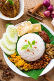 Nasi lemak kukus. Traditional malaysian spicy rice dish, fresh cooked with hot steam. Served with belacan, ikan bilis, acar, peanuts and cucumber. Decoration stock photo