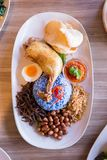 Nasi Lemak is a Malay fragrant rice dish cooked in coconut milk and butterfly pea served with fried chicken, fried small fish. Nasi Lemak is a Malay fragrant stock photos