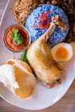 Nasi Lemak is a Malay fragrant rice dish cooked in coconut milk and butterfly pea served with fried chicken, fried small fish. Nasi Lemak is a Malay fragrant stock image