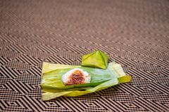 Nasi lemak is a Malay fragrant rice dish cooked in coconut milk and pandan or banana leaf. It is common food found in Malaysia Stock Photos