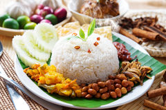 Nasi lemak malaysian dish. Nasi lemak traditional malaysian hot and spicy rice dish, fresh cooked with hot steam. Served with belacan, ikan bilis, acar, peanuts royalty free stock photography