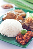 Nasi Lemak. Malaysian traditional spicy dish hot steamed rice nasi lemak served with sambal belacan, ikan bilis, acar, peanuts and cucumber Stock Photo