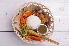 Nasi lemak / Nasi campur, Indonesian Balinese rice with potato fritter, sate lilit, fried tofu, spicy boiled eggs, and peanut Royalty Free Stock Photos