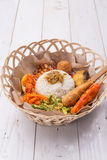 Nasi lemak / Nasi campur, Indonesian Balinese rice with potato fritter, sate lilit, fried tofu, spicy boiled eggs, and peanut. On wood base Stock Images
