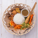 Nasi lemak/Nasi campur, Indonesische Balinese rijst met aardappelfritter, verzadigt lilit, gebraden tofu, kruidige gekookte eiere Stock Fotografie