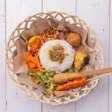 Nasi lemak/Nasi campur, Indonesische Balinese rijst met aardappelfritter, verzadigt lilit, gebraden tofu, kruidige gekookte eiere Stock Afbeelding