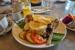 Nasi Lemak populär traditionell malajiska frukostmaträtt inklusive kokosnötris, det pandan bladet, det stekte ägget, grillade ans Arkivbilder