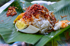 Nasi Lemak. Popular local cuisine in Malaysia. Wrapped in banana leaf, nasi lemak is served with the spicy sambal, fried anchovies, peanut and also cucumber Stock Images