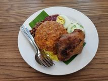 Nasi lemak serve with fried chicken,egg,anchovies,cucumber sliced,sambal and ground nuts stock photos