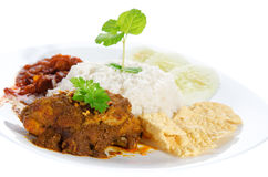 Nasi lemak traditional malay food. Nasi lemak is traditional malaysia spicy rice dish. Served with belacan, ikan bilis, acar, peanuts and cucumber. Isolated on stock photo