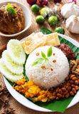 Nasi lemak. Traditional malaysian spicy rice dish, fresh cooked with hot steam. Served with belacan, ikan bilis, acar, peanuts and cucumber. Decoration setup royalty free stock images
