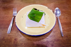 Nasi Lemak. A wrapped nasi lemak in a metal plate on a dining table stock photography
