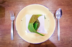 Nasi Lemak. A wrapped nasi lemak in a metal plate on a dining table stock photos
