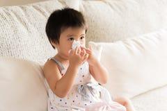 Naso di pulitura o di pulizia della piccola ragazza asiatica malata con il tessuto immagini stock