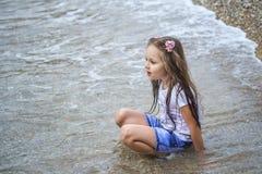 Nass kleines Mädchen, das im Wasser sitzt lizenzfreies stockbild