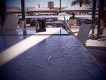 Nass Restaurantstühle und -tabelle nach dem Regen mit einem enormen Strahl des Lichtes lizenzfreie stockfotografie