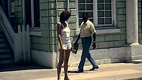 Nassau streets Bahamas. Nassau, Bahamas - Circa 1978: Bahamas Nassau town streets in New Providence island with vintage cars and tourists walking by the road in stock footage