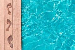 Nasse Abdrücke auf der Plattform eines Swimmingpools Stockfotos