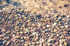 Nasse Kiesel auf der Strandweinleseart Stockbild