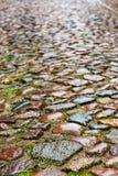 Nasse Kopfsteine auf einer mittelalterlichen Straße, vertikales Hintergrund textu Lizenzfreies Stockfoto