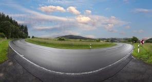 Nasse kurvenreiche Straße in ländlicher Eifel-Landschaft Lizenzfreies Stockbild