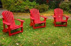 Nasse rote Adirondack-Stühle in einem Rasen Stockbilder