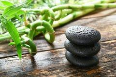 Nasse schwarze Poliermassage-Steine auf Bambus im Badekurort Stockfoto