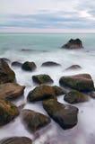 Nasse Steine auf dem See am Sonnenaufgang Stockfoto