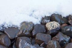 Nasse Steinkiesfläche, die frischen Schnee schmilzt Stockbilder